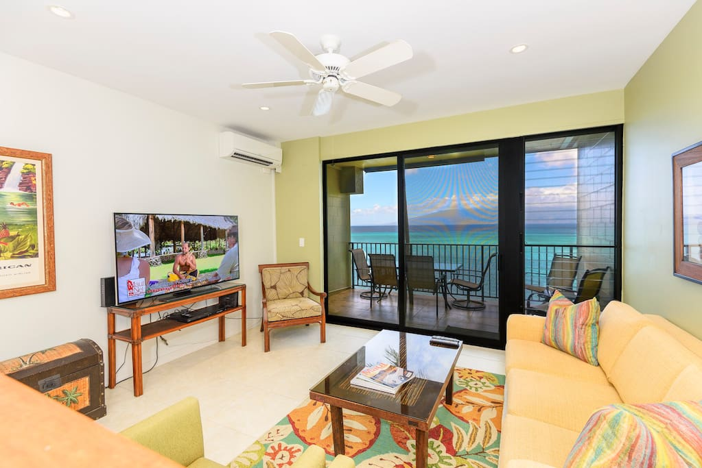 Living room features a flat screen TV ad a stunning ocean view