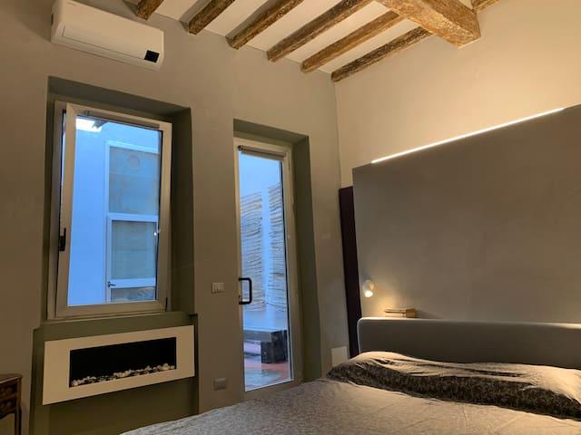 Camera da letto matrimoniale con caminetto e soffitto con travi antiche a vista.