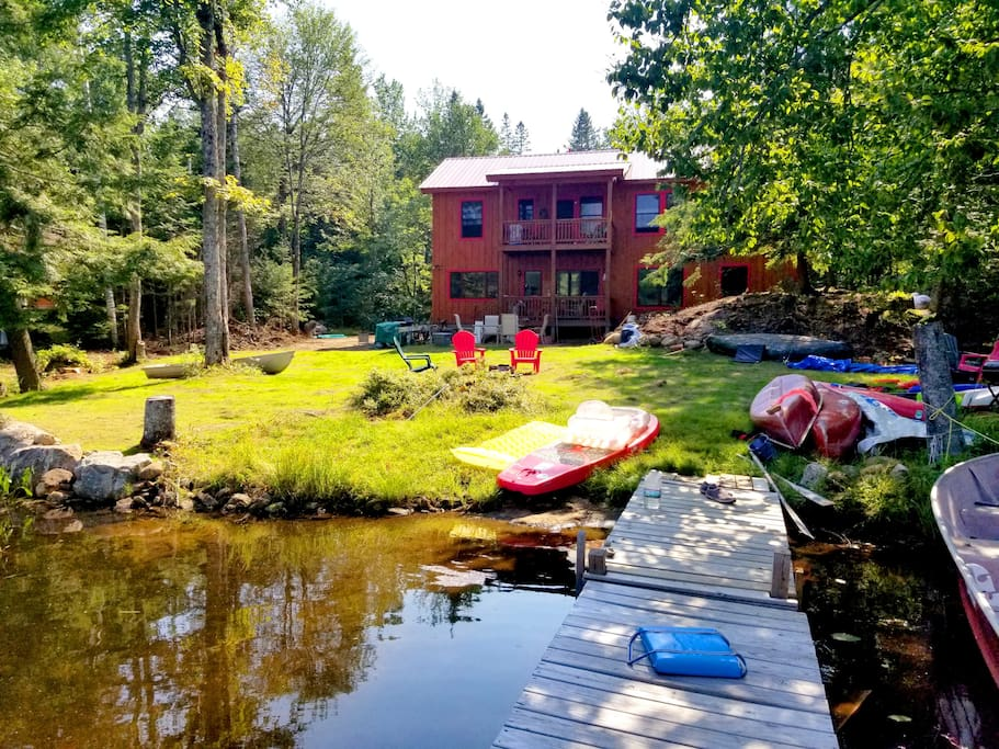 Large lakeside yard with boat dock, beach, tiled dining/BBQ patio, hammock, fire pit, 2 canoes, 2 kayaks, 1 SUP, 1 boat, & several inflatables included
