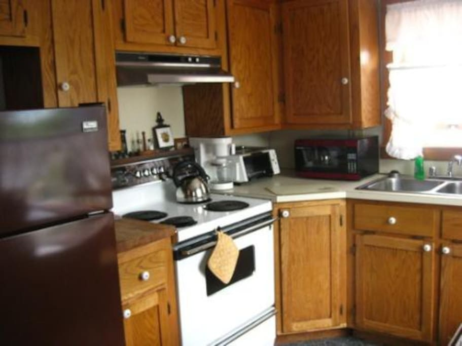 The kitchen in the cottage is fully equipped with a refrigerator, freezer, oven, and microwave.
