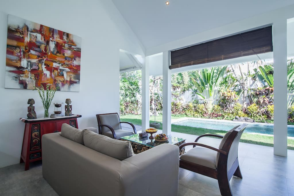 Open living room with a view on the private pool and garden
