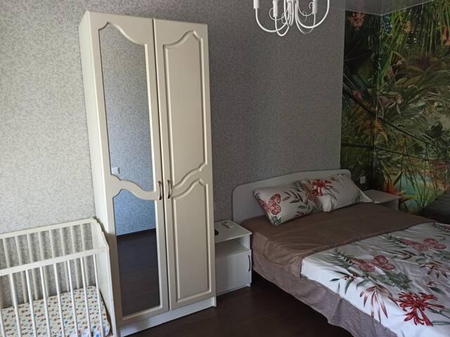 Комната номер 1 на первом этаже, где расположены одна двухспальная кровать и одна детская кроватка. Телевизор, сплит система.