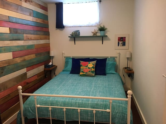 2nd Bedroom features a comfortable Queen bed and hardwood feature wall.