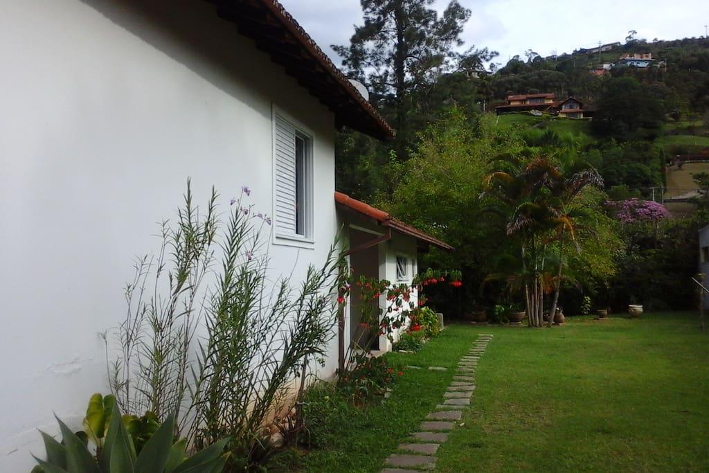 Vista lateral da casa. Jardim e estacionamento.
