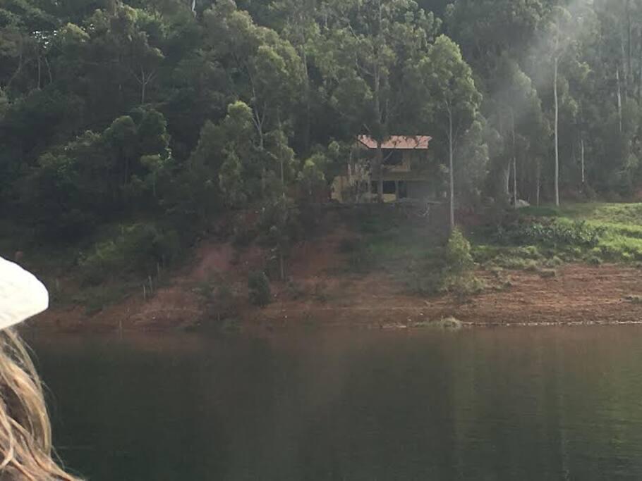 Esta é a CASA C vista a partir da represa - rodeada de árvores e natureza