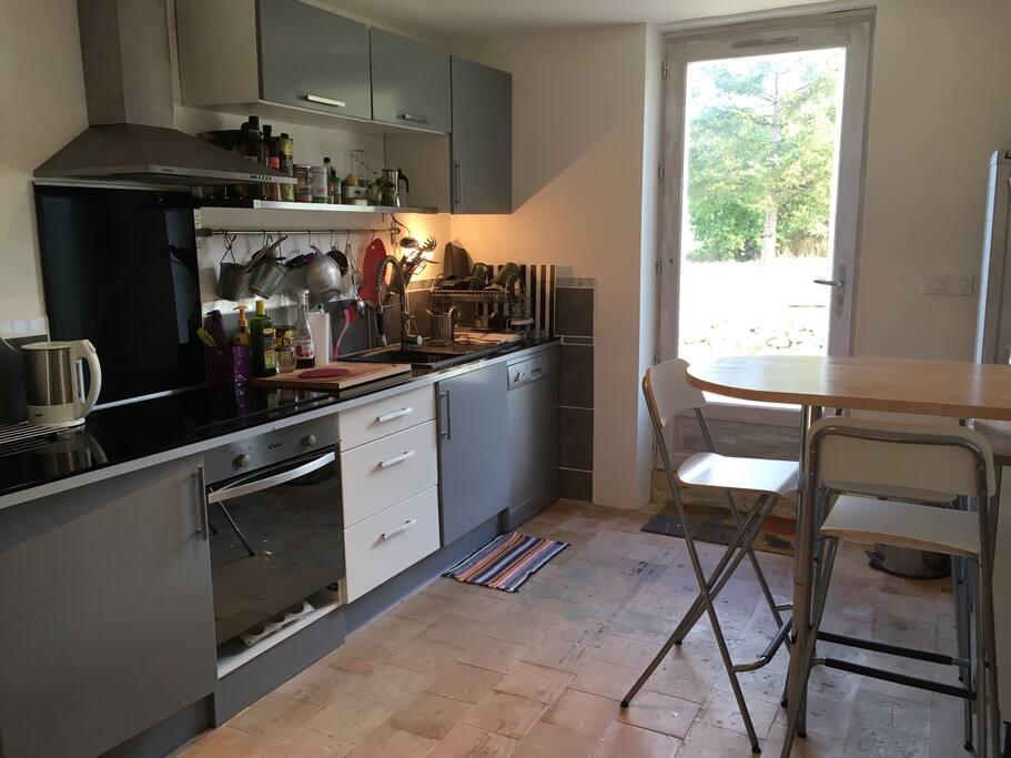 La cuisine équipée avec plaque, four, lave vaisselle, micro ondes, frigo congélateur, bouilloire, grille pain.