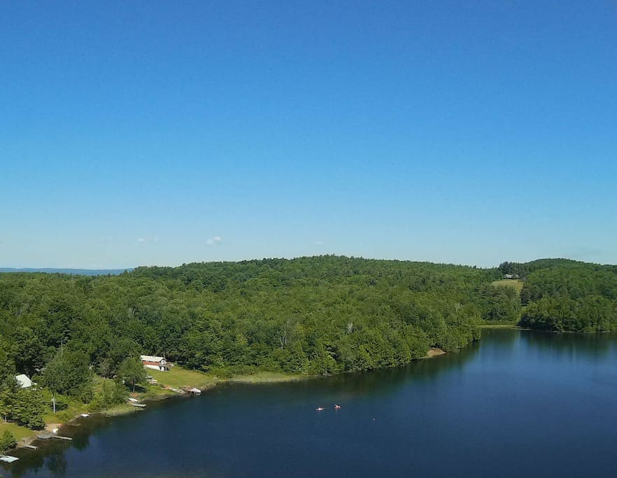 This is an aerial view of the house and lake during a bright summer day.