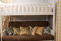The futon couch folds out into a full-sized mattress. Above it is a single bunk, which is a twin sized mattress.