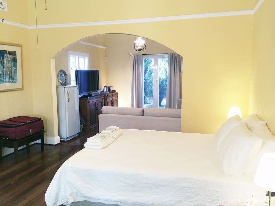 Queeen size bed in large room with adjoining TV and sitting room