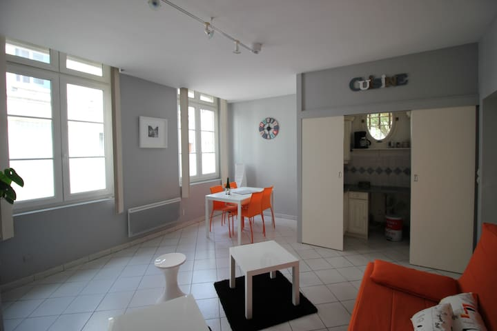 Séjour salon avec vue sur le coin cuisine séparé par des portes coulissantes.