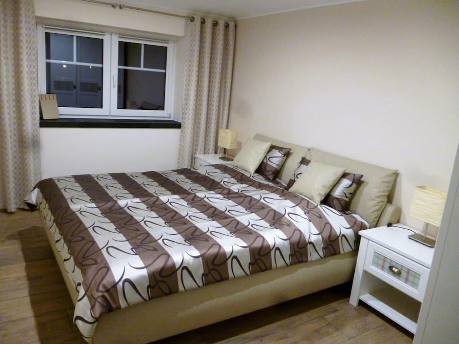 Schlafzimmer mit Doppelbett, Nachtschränkchen und Kleiderschrank.