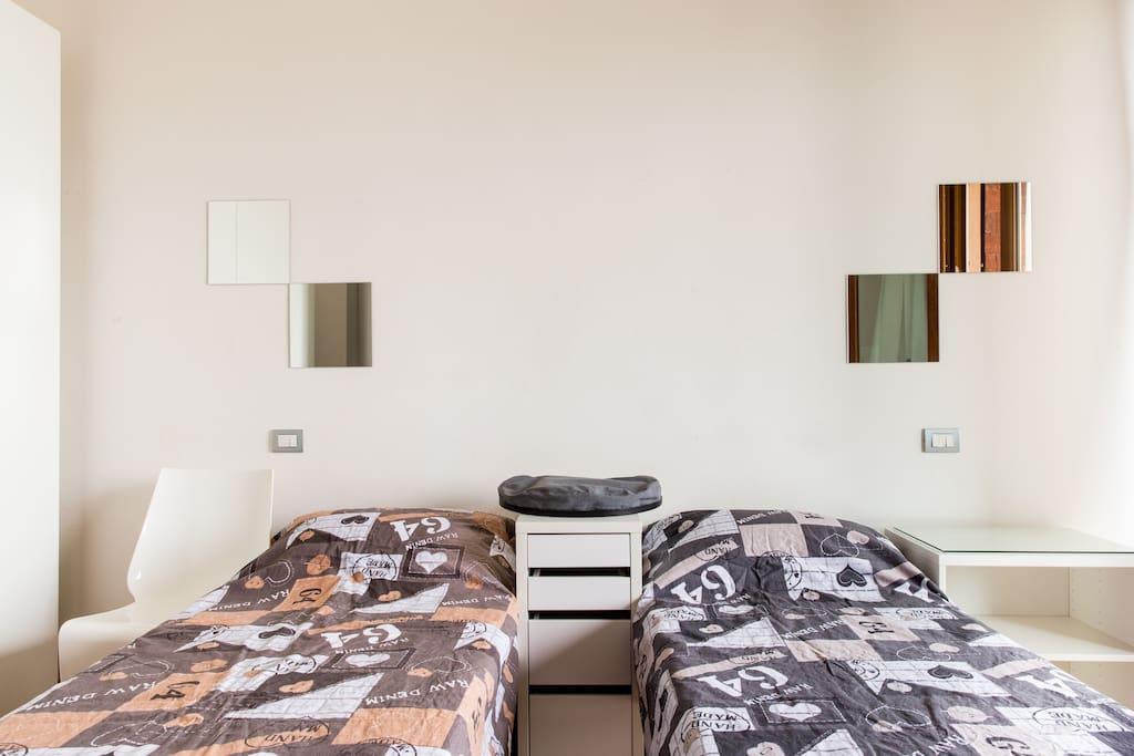 Stanza 1 Ampia doppia con letti singoli, che diventano matrimoniali all'occorrenza, bagno in camera e terrazzino, vetri insonorizzati per il massimo relax. Bilocale