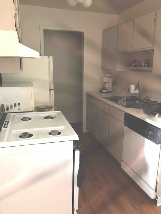this is the kitchen with a microwave a gas stove and a dishwasher that are available for you to use. feel free to cook here as well also a refrigerator included
