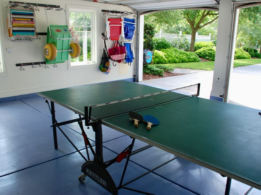 Two car garage with fold up ping pong table and beach supplies.