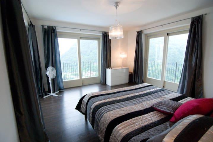 master bedroom with 2 sets windows & balcony