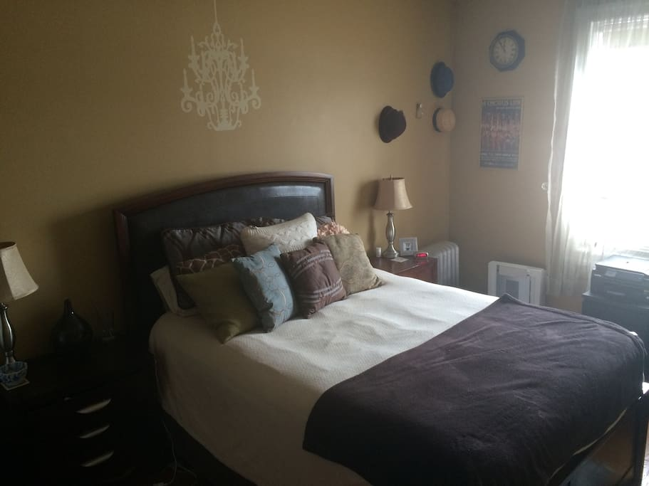 Large bedroom with queen bed and lots of morning light. Also has desk with outlets and printer/scanner.