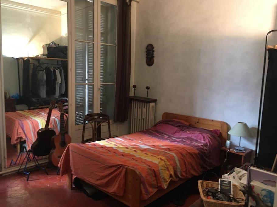 Chambre agréable avec deux petits balconnets, un lit deux places, un bureau de travail et une penderie accessible.