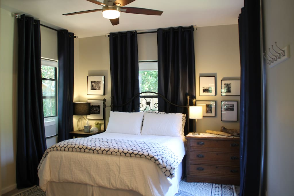 very comfortable Queen bed, two lamps, remote controls for the AC unit and the overhead fan and light, beautiful light from 3 windows all with roller shades and high quality navy blue room darkening curtains.