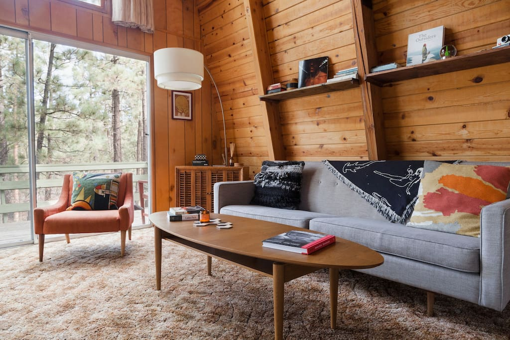 The living room is large and open with floor to ceiling views of the trees that surround the cabin. Seating all around the room is perfect for great talks with even greater people.