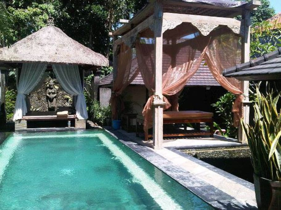 Pool with massage area, gazebo in the back and water feature in the back