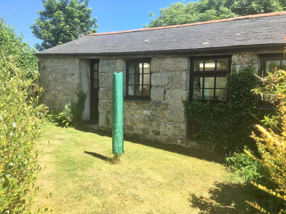 The beautiful granite construction is on full display at the rear of Trethellan Cottage.  View shows back garden with door from kitchen and windows from lounge area