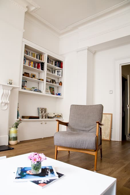 Spacious, very bright living room with two large high-ceiling windows, and original wooden shutters