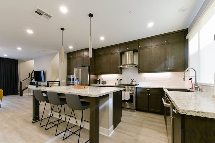 Brand new kitchen with stainless steel appliances and quartz counters, pots, pans, and utensils for enjoying meals at home