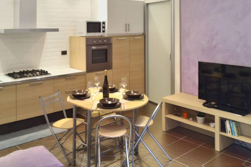 La zona giorno e la cucina con tavolo da pranzo/ Living area with kitchen and dining table