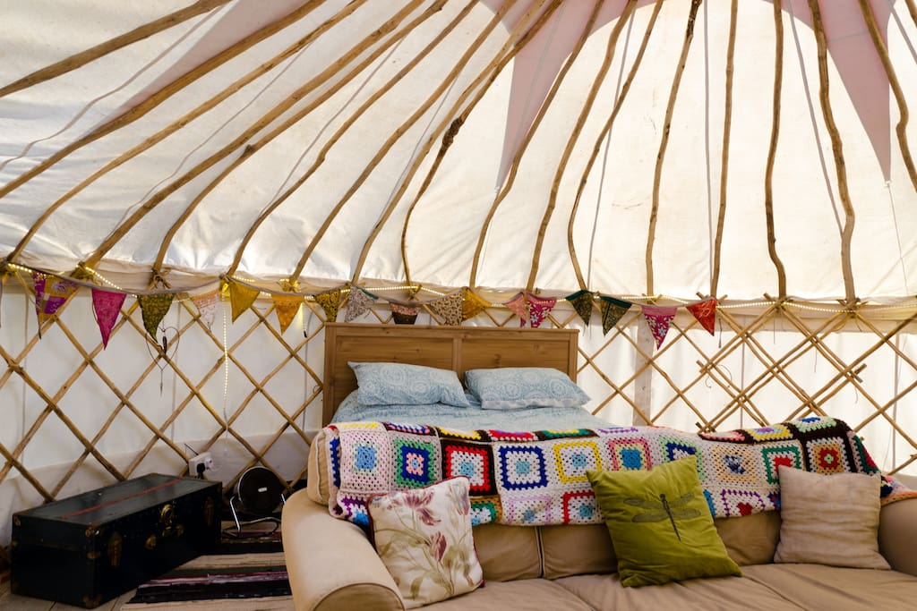 Inside the yurt with king size bed and large sofa for romantic nights in