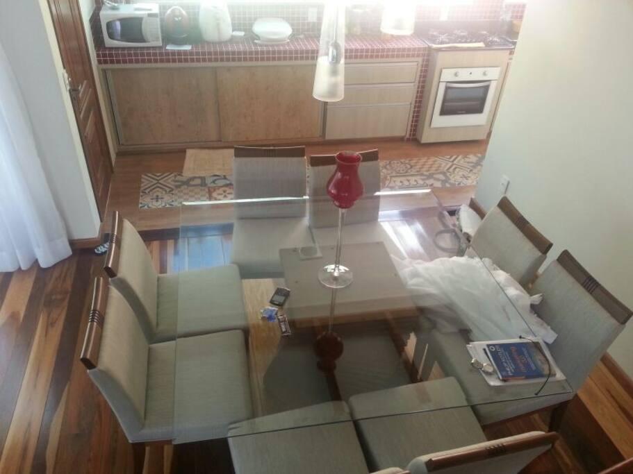 sala de jantar com oito cadeiras. Cozinha estruturada para jantares de negócios.