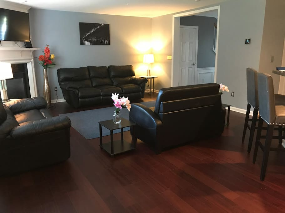 Living room hardwood floors & black leather furniture with twin  pull out bed.