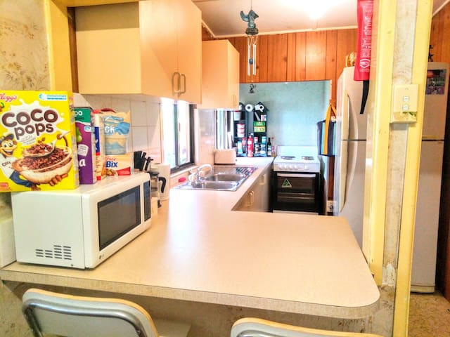 A cosy kitchen, microwave, hot plates & oven, with a family fridge freezer