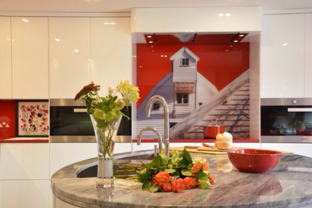 Kitchen - showing the stunning glass splash back image of the mill and is the focal point of the kitchen where the oblong miele hob is and 2 miele wide ovens on either side an exquisite kitchen to use having everything you should need