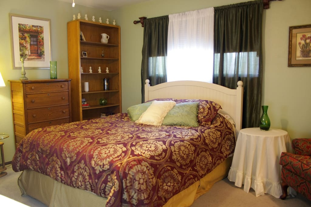 Guest room with Queen-sized bed, oak dresser and bookcase.