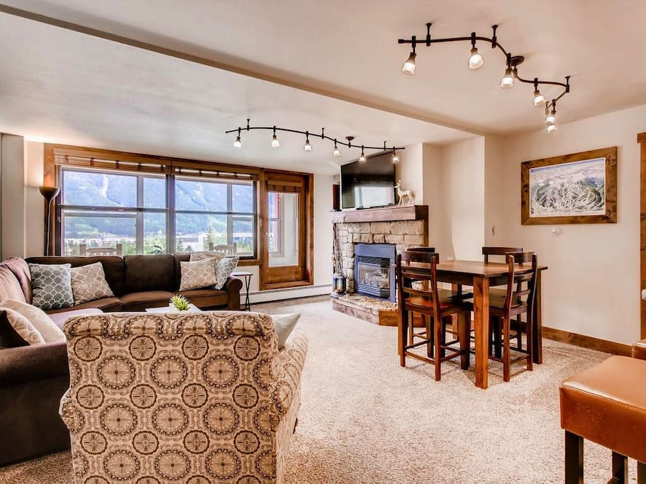 Living room with view of seating, fireplace, flatscreen TV and the Sunroom