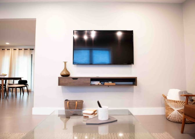 Smart TV against living mounted against living room wall. Enjoy plenty of complimentary options such as Netflix, Hulu, HBO, Disney+ ... you name it we have it for you!