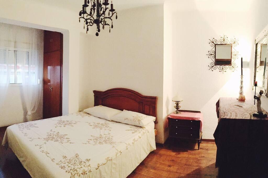 Amplio dormitorio principal con ventana al exterior, cómoda cama de látex, armario y aparador.