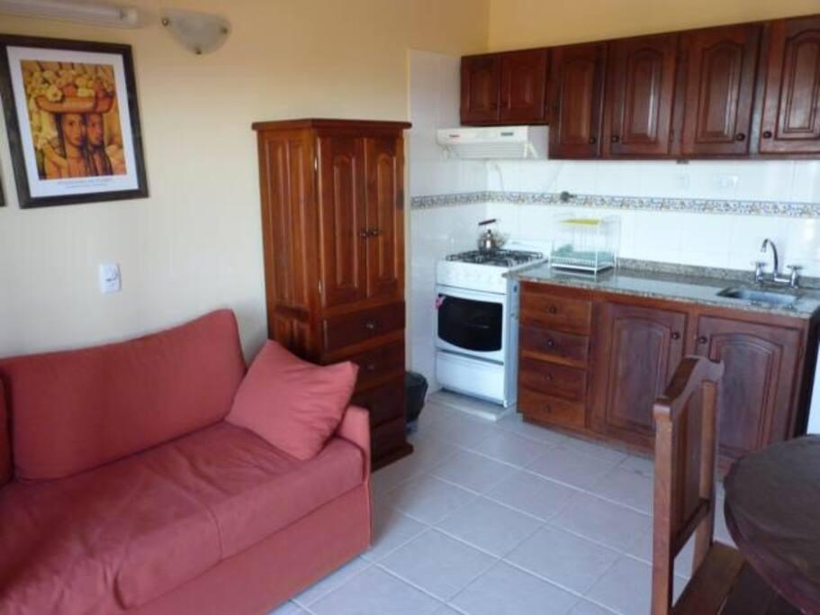 Living comedor con cocina, microondas, heladera con freezer , y TV por cable, y ventilador de techo.