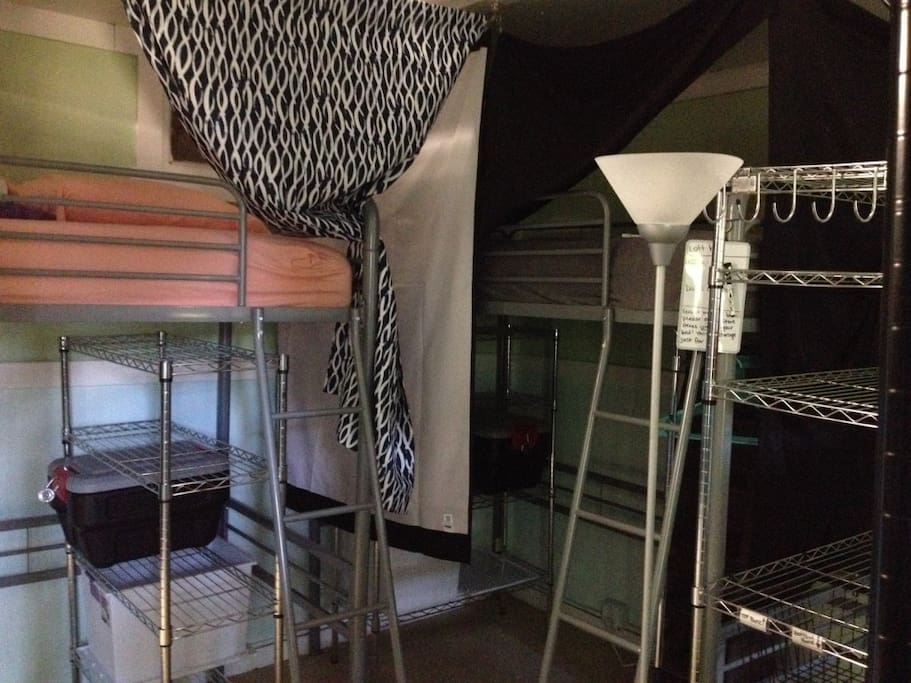 View of two loft beds in room. Loft beds have reserved storage underneath the bed. The storage includes clothes rack/hangers, cloth shelves, metal wire shelves, black lockable bin, and a  storage bin.