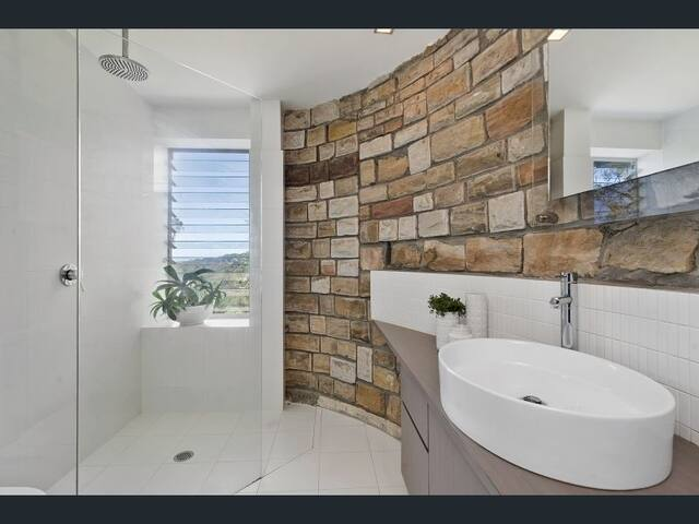 Main bathroom with louvre windows that open to feel like your showering amongst the trees. Curved, sandstone feature wall, rain shower & heated towel racks