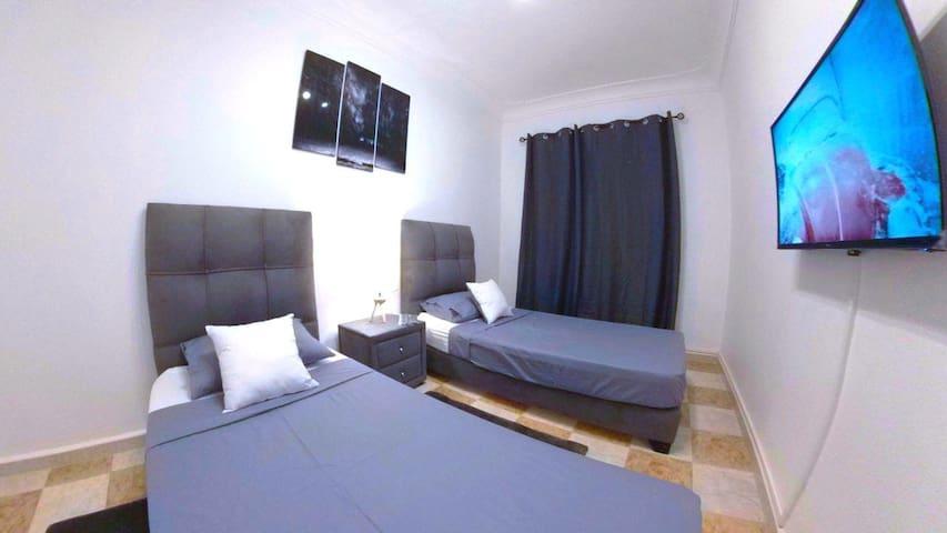 deuxième chambre à deux lits de 90cm sur 2m chacun, un téléviseur à écran plat accroché au mur.