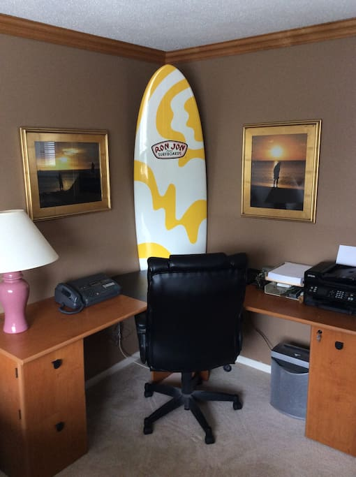 Desk in room and my surf board that never has seen water