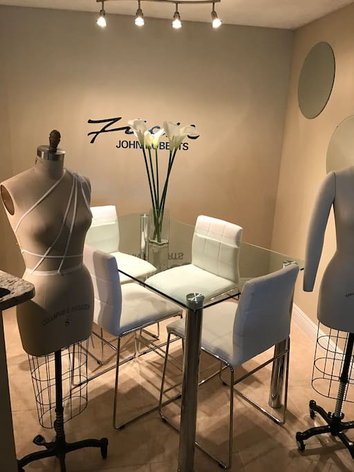 Modern dining room with white leather stools and glass and chrome bar table. The back wall contains my logo keep me inspired when designing clothes with the dress forms.