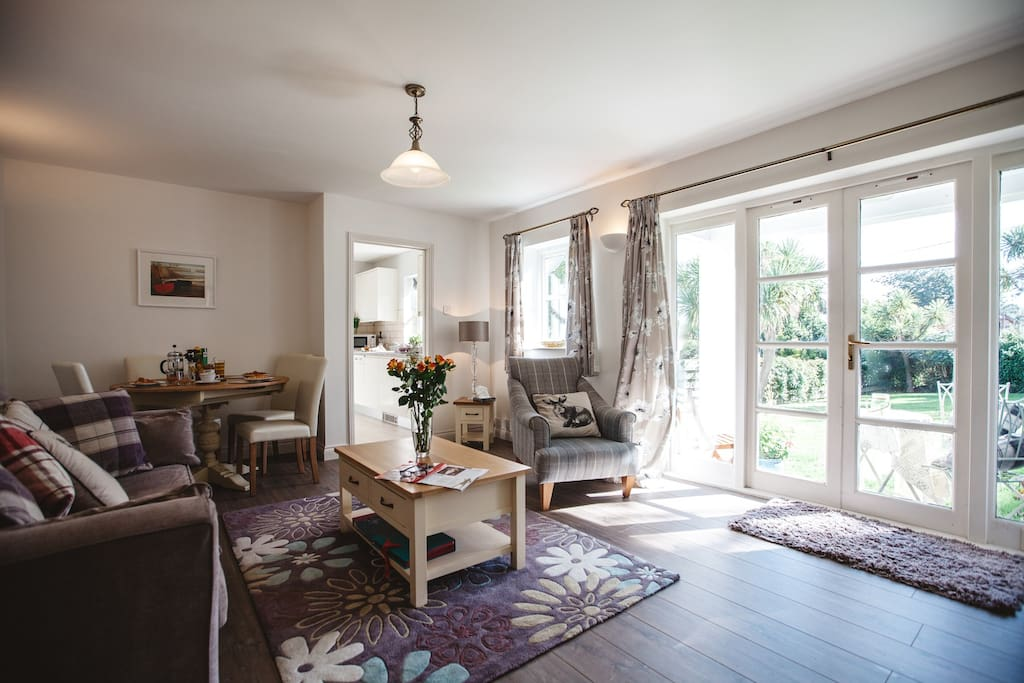 Living / dining area, with french windows, onto your patio, large garden and views over the village to the sea.