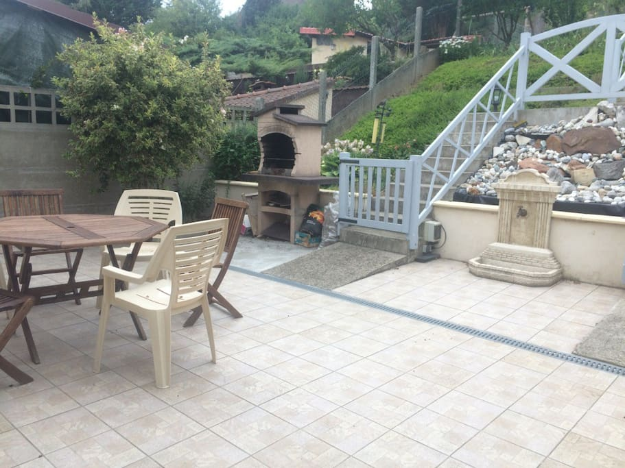 Terrasse de la maison avec barbecue et cascade. Terrace, backyard with B.B.Q and fish pond