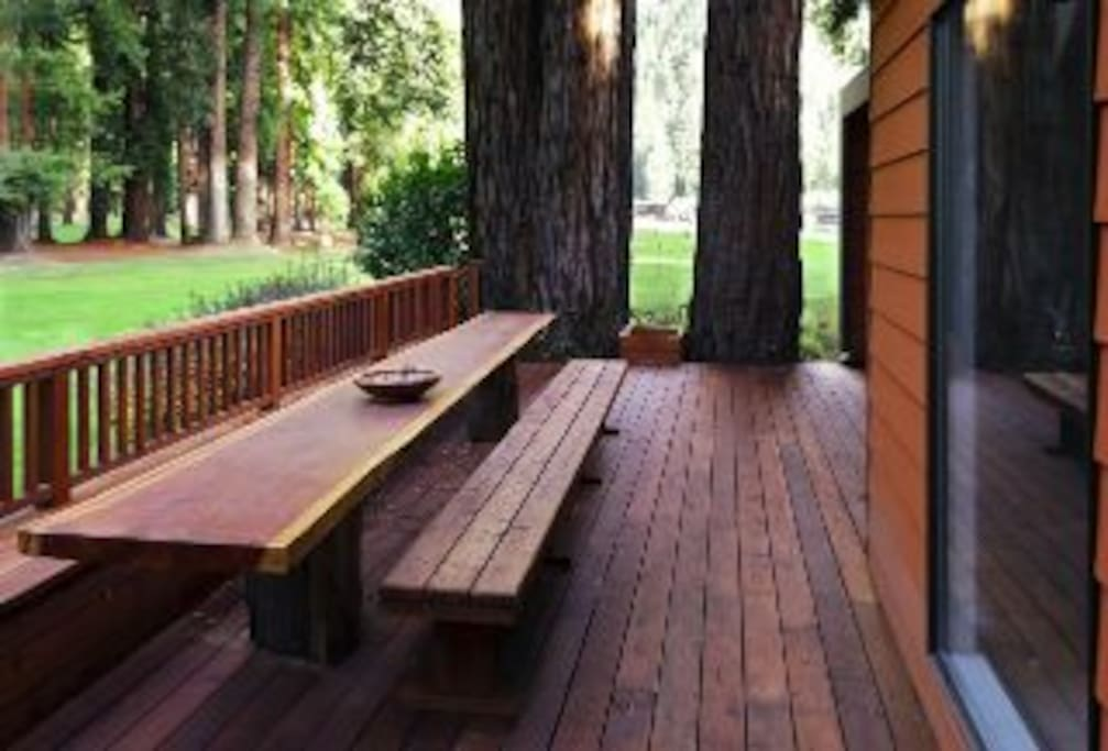 The back patio overlooks a golf course and has a gorgeous long table made of redwood.