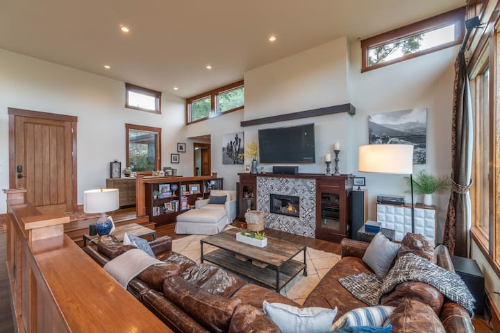 """This cozy living room includes a modern tiled gas fireplace, 82"""" TV, surround sound, record player, big comfy reading chair and huge deep leather sectional."""