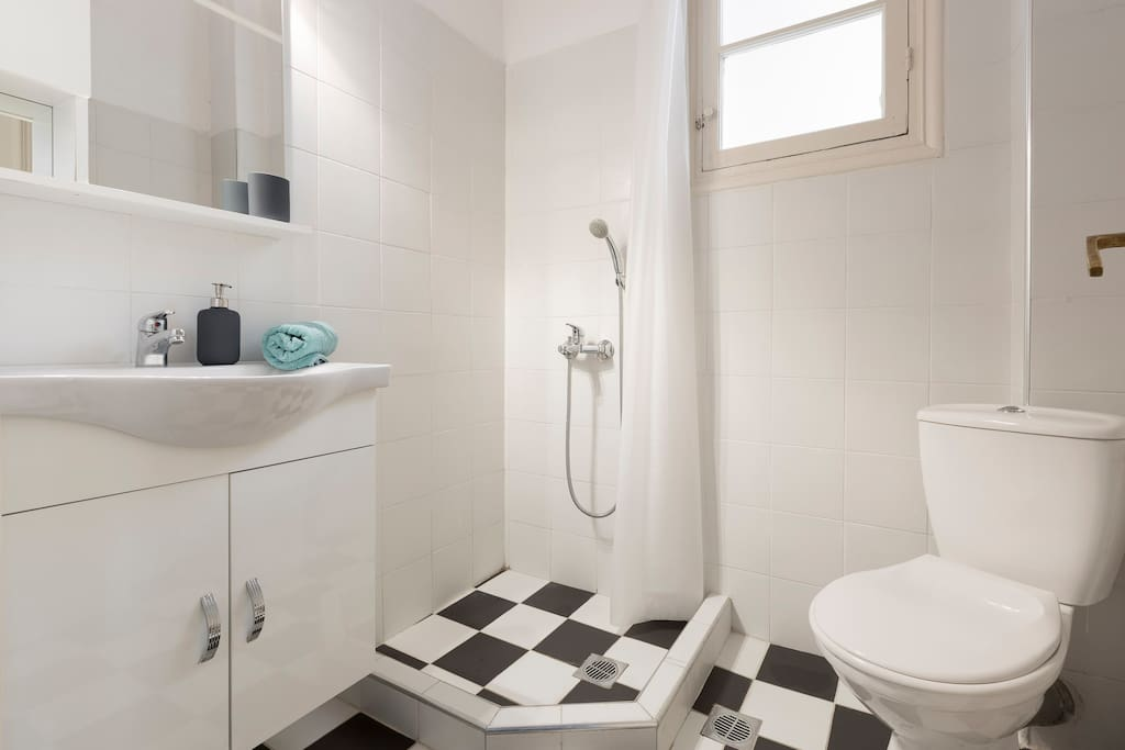 Comfortable toilet and shower with black and white floor tiles and big window to renew the air of the bathroom