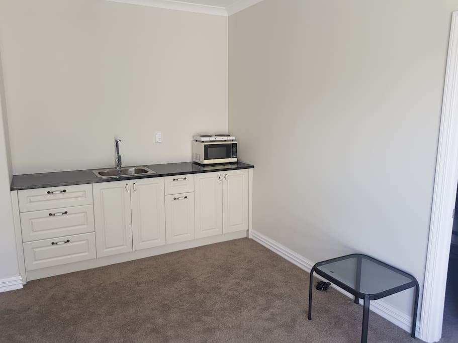 Private Kitchen area with Sink/ Microwave/Fridge/Hot Plate/Kettle/Toaster/Pans/Plates/Cups etc. Includes a dining table and chairs.