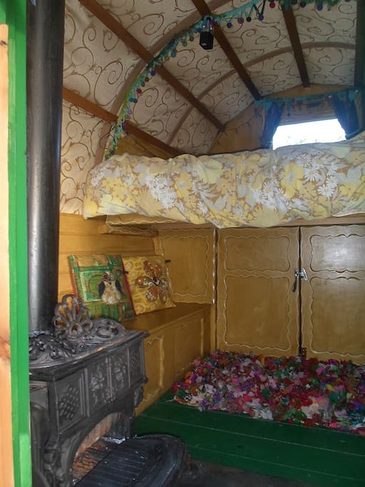 Inside the gypsy wagon, little log burner, large cupboard, one of the bench seats, and bed